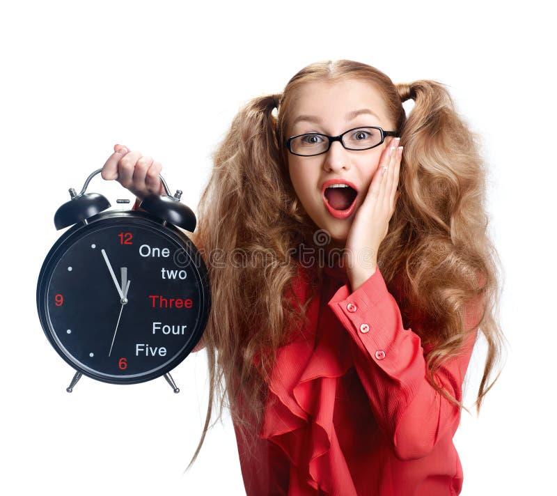 Härlig flicka i exponeringsglas med en stor klocka i nöd royaltyfri foto