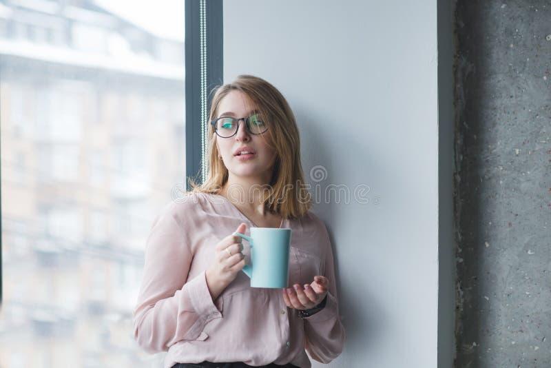 härlig flicka i exponeringsglasställningarna i väggen nära fönstret med en kopp kaffe arkivfoton