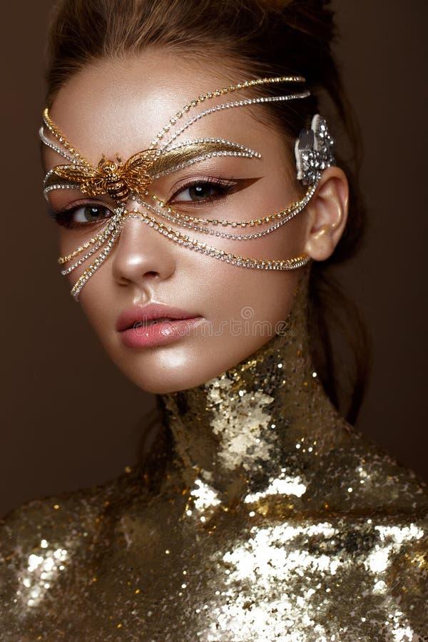 Härlig flicka i guld- maskering och ljust aftonsmink Härlig le flicka fotografering för bildbyråer