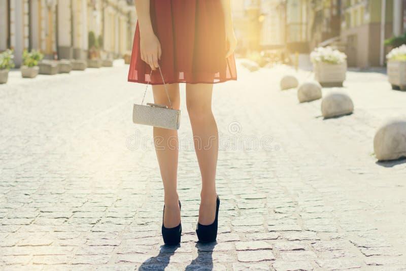 Härlig flicka i handväskan för aftonklänning som väntar i gata close royaltyfria foton