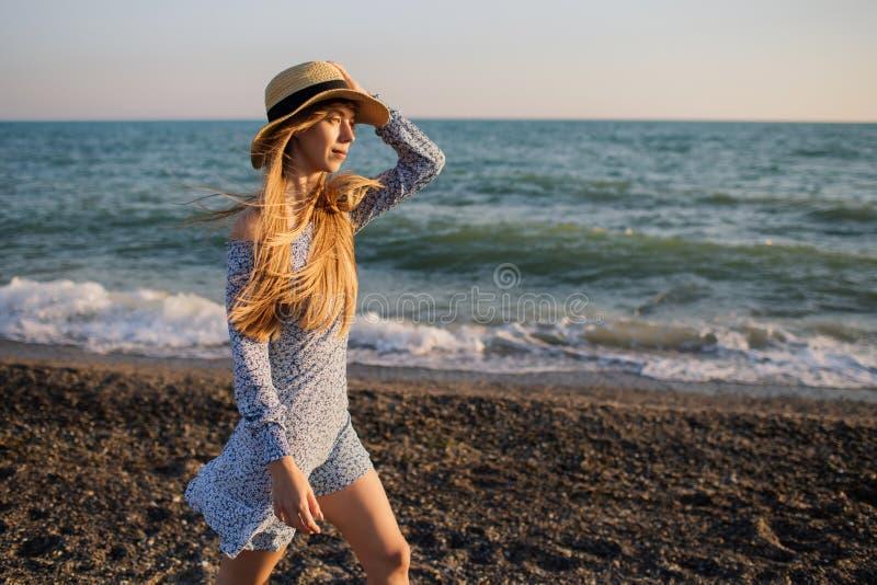 Härlig flicka i hatt som promenerar stranden royaltyfria bilder