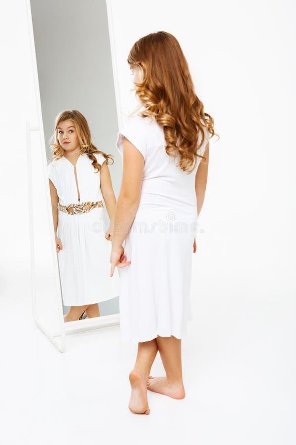 Härlig flicka i klänningen som framme står av spegeln royaltyfria bilder