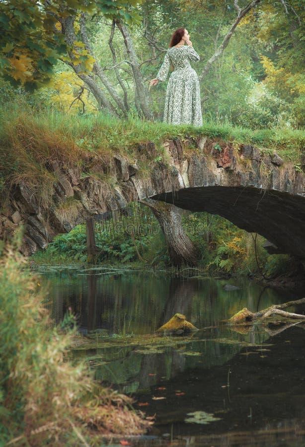 Härlig flicka i medeltida klänninganseende på bron nära riv royaltyfria bilder