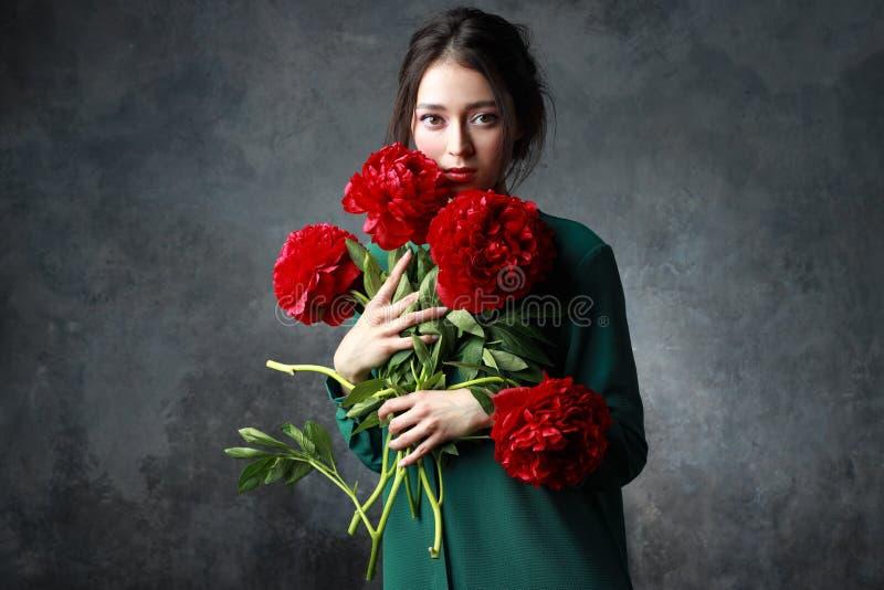 Härlig flicka i mjuk grön klänning med bukettblommapioner i händer Sk?mtsam modemodell som ser kameran fotografering för bildbyråer