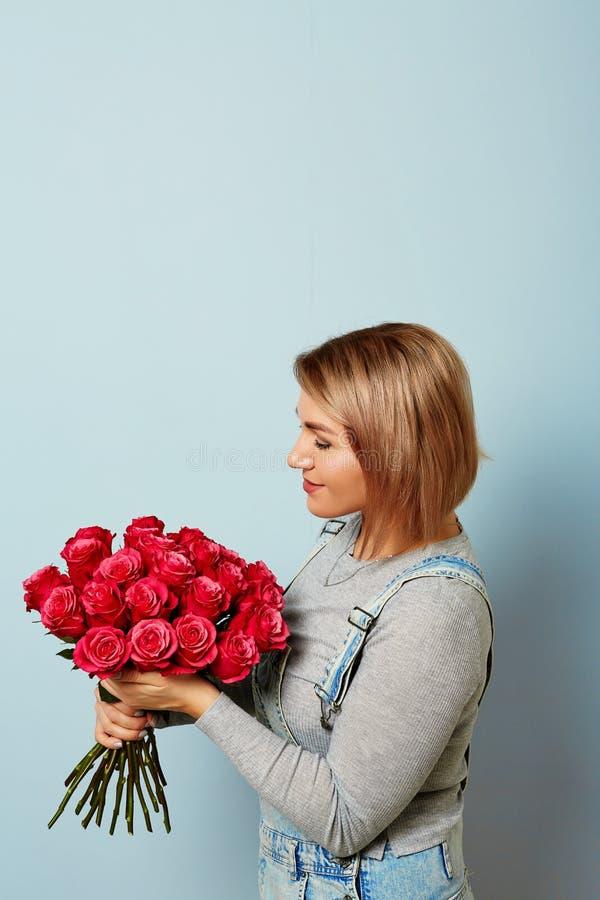 Härlig flicka i overallerna med röda rosor i händer på en blå bakgrund Händer för kvinna` s rymmer en bukett av arkivfoton