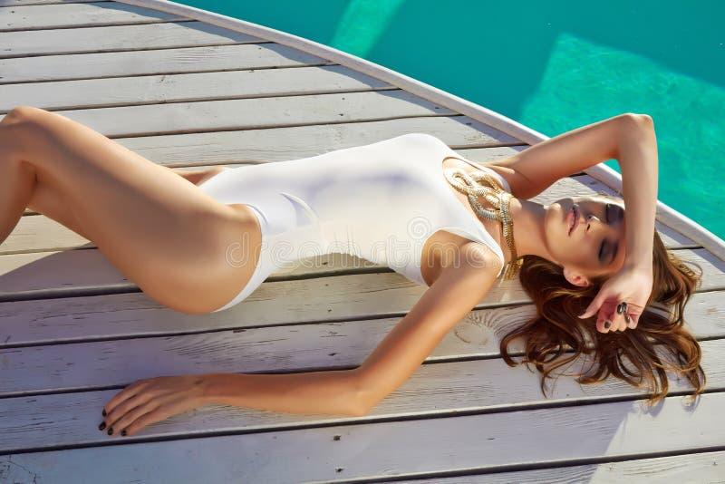 Härlig flicka i perfekt solbränd hud för bra form nära simbassäng arkivbild