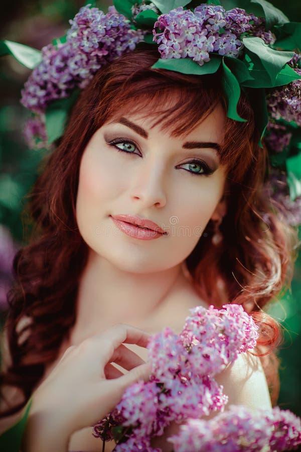Härlig flicka i purpurfärgad klänning med lila blommor fotografering för bildbyråer