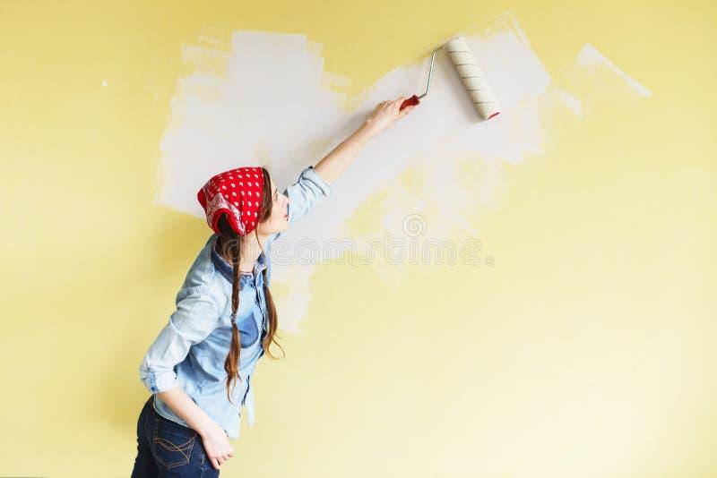 Härlig flicka i röd huvudbindel som målar väggen med målarfärgrulle arkivfoton