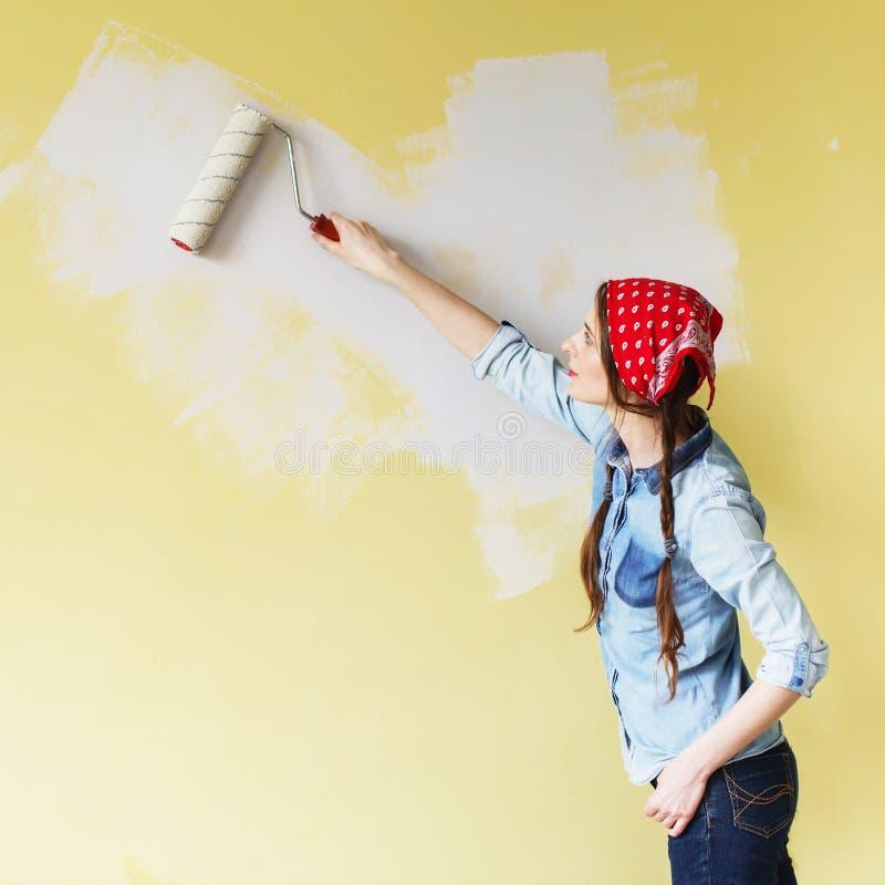 Härlig flicka i röd huvudbindel som målar väggen med målarfärgrulle royaltyfria foton
