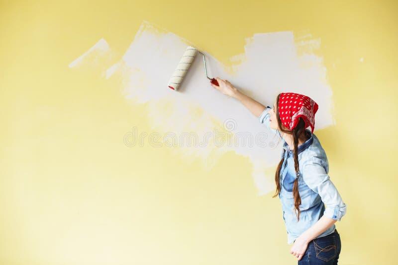 Härlig flicka i röd huvudbindel som målar väggen med målarfärgrulle royaltyfria bilder