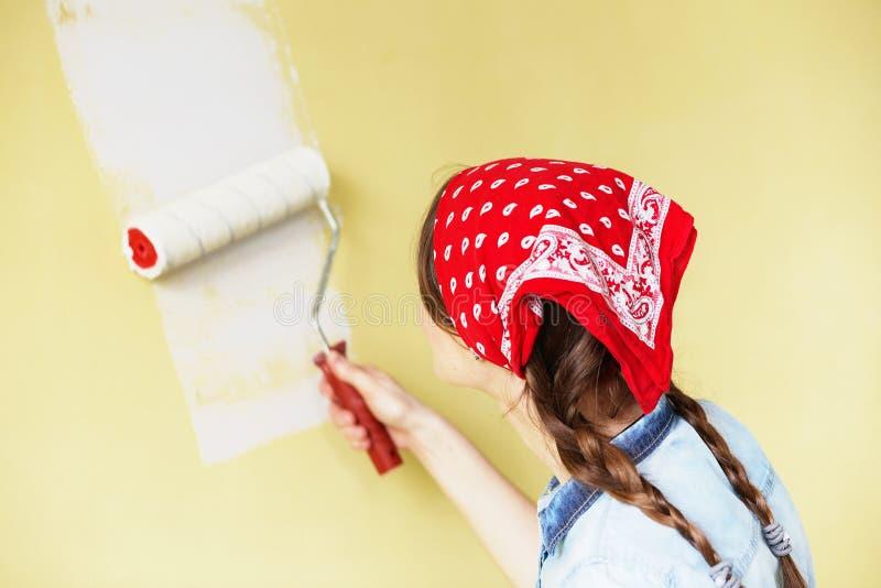 Härlig flicka i röd huvudbindel som målar väggen med målarfärgrulle arkivfoto