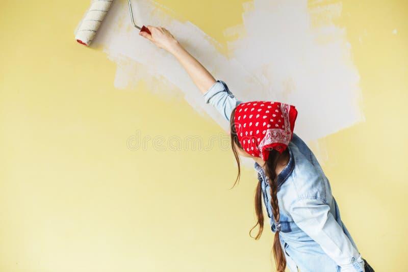 Härlig flicka i röd huvudbindel som målar väggen med målarfärgrulle fotografering för bildbyråer