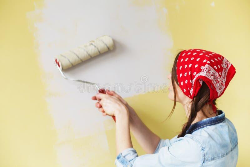 Härlig flicka i röd huvudbindel som målar väggen med målarfärgrulle arkivbild