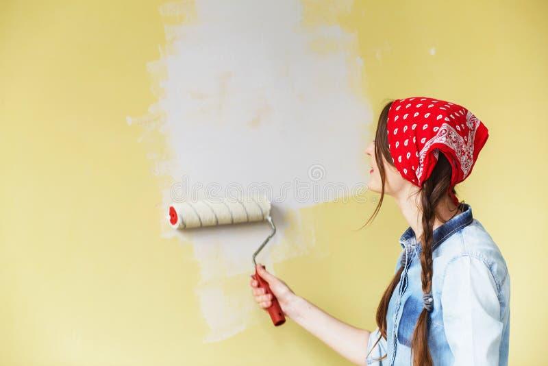 Härlig flicka i röd huvudbindel som målar väggen med målarfärgrulle arkivbilder