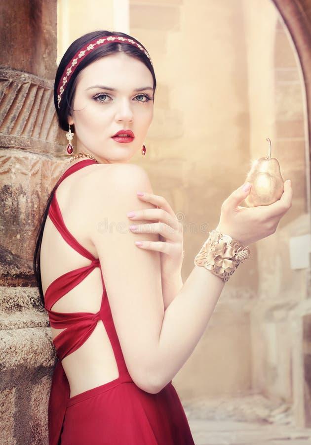 Härlig flicka i röd klänning och smycken royaltyfri bild