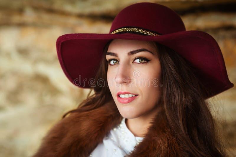 Härlig flicka i rödbrunt slut för filthatt upp ståenden barn för for för liemannoutbook utomhus- Se kameran arkivbilder