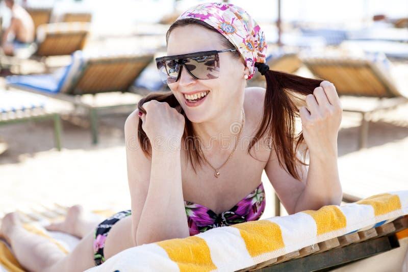 Härlig flicka i solglasögon som ligger på stranden royaltyfria bilder