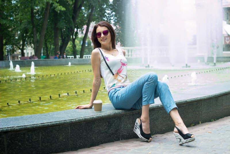 Härlig flicka i solglasögon som sitter nära springbrunnen royaltyfri bild