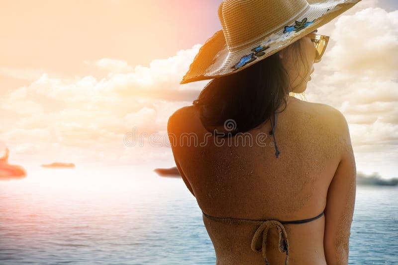 Härlig flicka i sugrörhatt och solglasögon som tycker om frihet på en sommarstrand arkivfoton