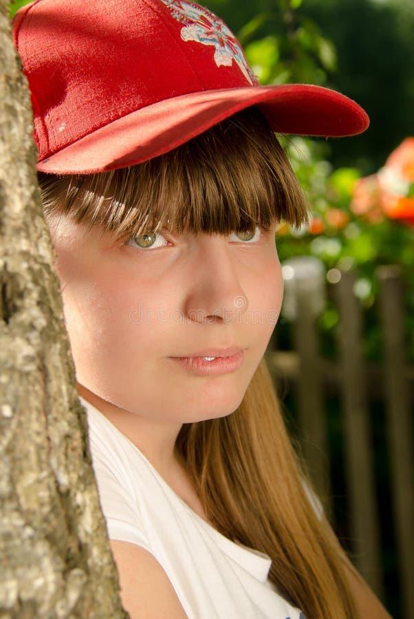 Härlig flicka i trädgården nära trädet som är tonårigt royaltyfria foton