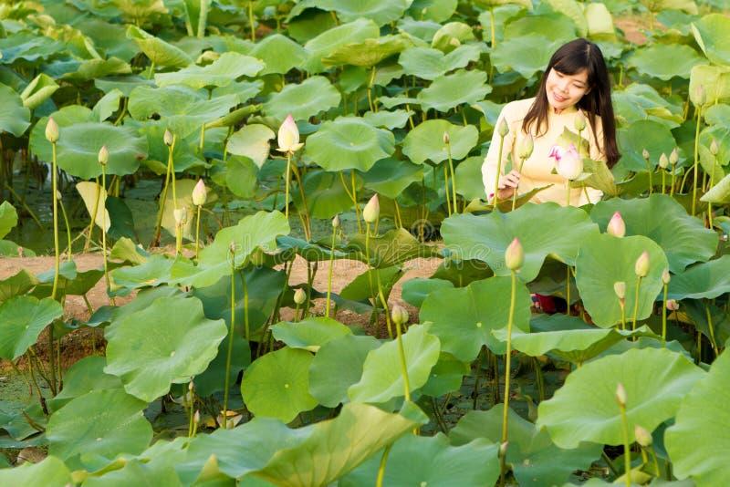 Härlig flicka i traditionsklänninglekar i lotusblommaträdgården royaltyfria foton