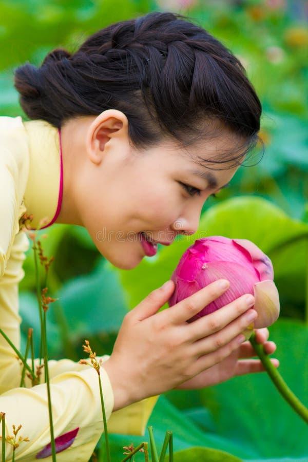 Härlig flicka i traditionsklänninglekar i lotusblommaträdgården royaltyfri fotografi