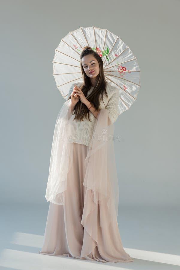 härlig flicka i trendigt vinterdräktanseende med det japanska paraplyet arkivfoton