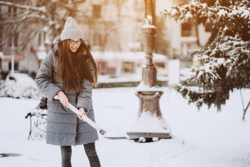 Härlig flicka i vintermodekläder med en skyffel arkivbilder
