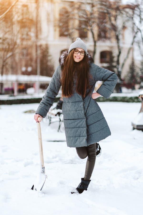 Härlig flicka i vintermodekläder med en skyffel royaltyfria bilder