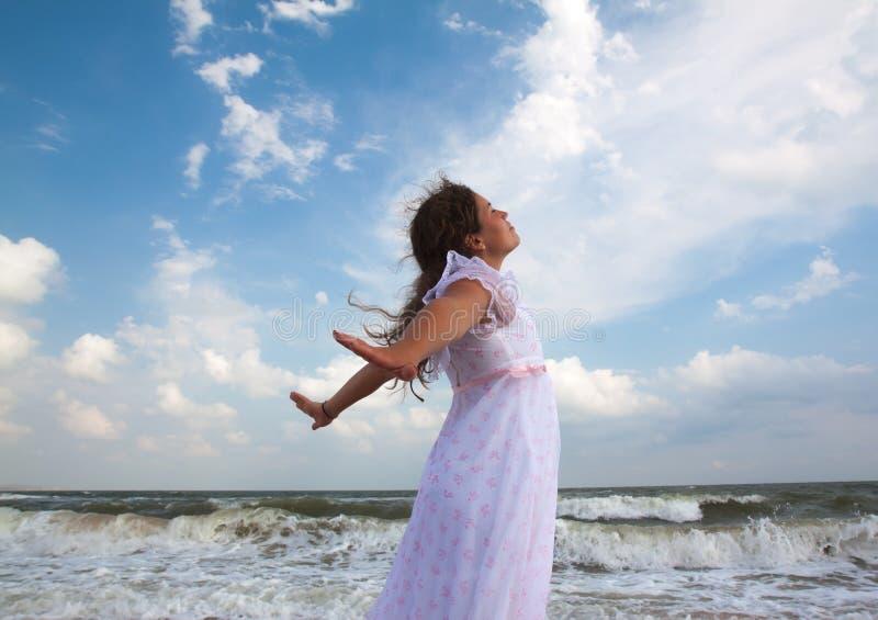 Härlig flicka i vit på den soliga stranden Frihet royaltyfria bilder