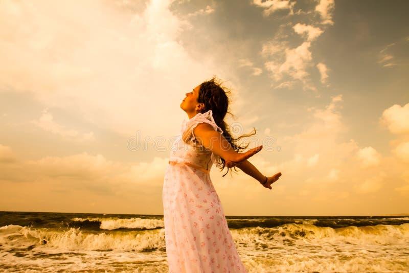 Härlig flicka i vit på den soliga stranden Frihets- och fredbegrepp royaltyfria foton