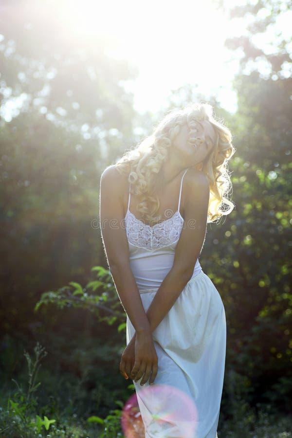 Härlig flicka i vitklänning som går på ängen i sommaren da fotografering för bildbyråer