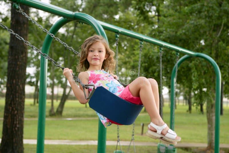 härlig flicka little leka swing arkivfoton