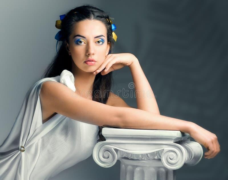 Härlig flicka med blommor i bilden av en forntida gudinna royaltyfri bild