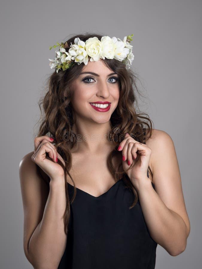 Härlig flicka med blommor i hår som poserar i den svarta skjortan som ser kameran royaltyfri bild