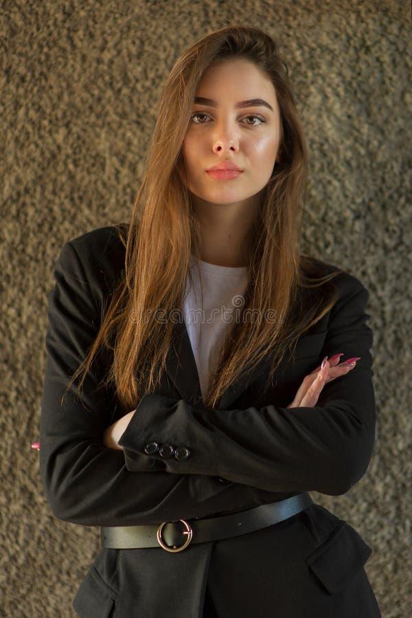 Härlig flicka med brunt långt hår i ett svart lag Dam nära den gråa väggen fotografering för bildbyråer