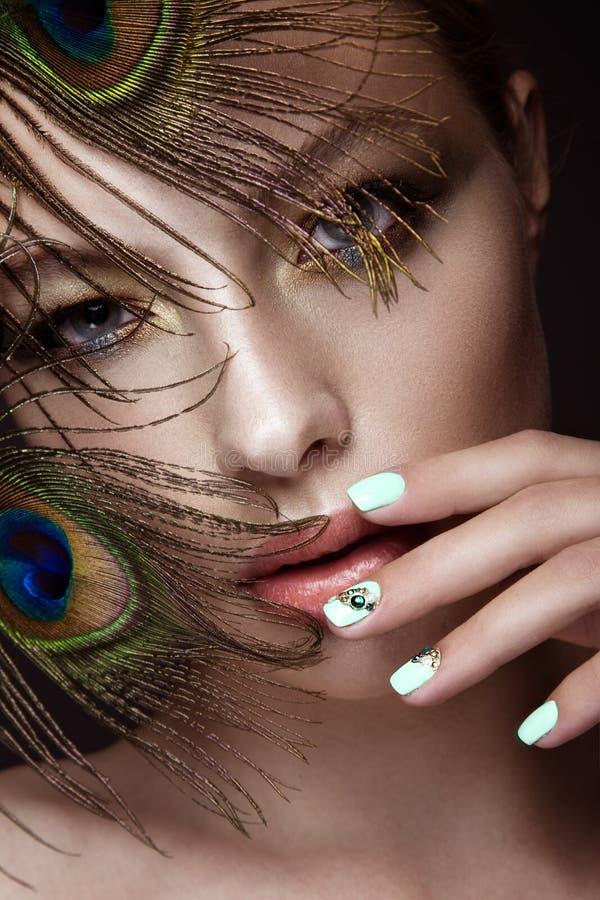 Härlig flicka med den ljusa makeup, manikyrdesign och påfågelfjädern på hennes framsida Konst spikar fotografering för bildbyråer