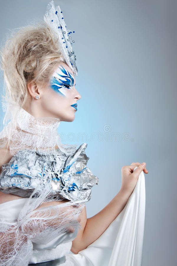 Härlig flicka med det idérika sminket för det nya året Barn härlig kvinna som blåser snow in mot kamera på vinterbakgrund royaltyfria foton