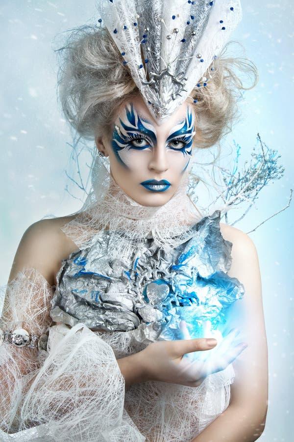 Härlig flicka med det idérika sminket för det nya året Barn härlig kvinna som blåser snow in mot kamera på vinterbakgrund fotografering för bildbyråer