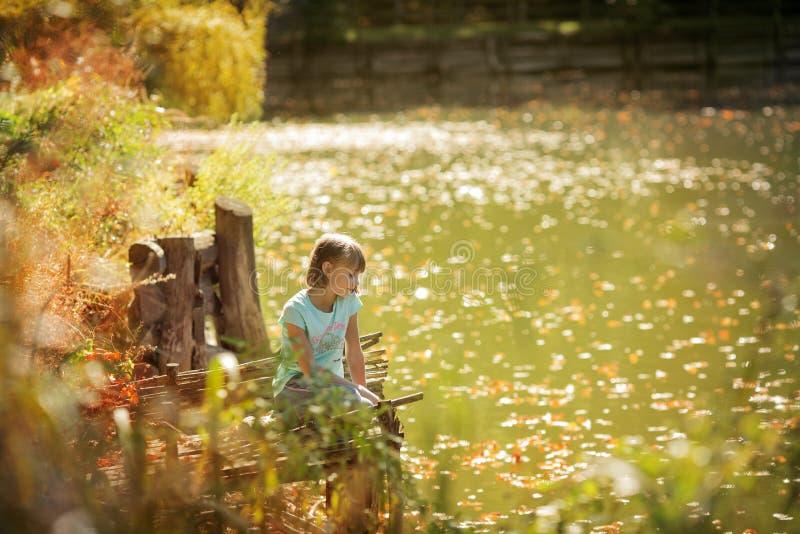 Härlig flicka med Down Syndrome som äter havre på naturen arkivfoto