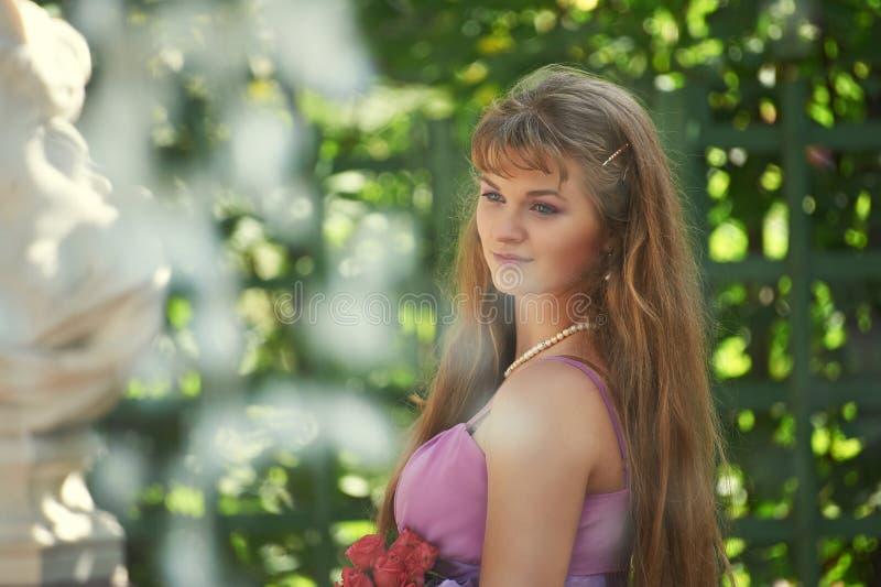 Härlig flicka med en bukett av rosor royaltyfri bild