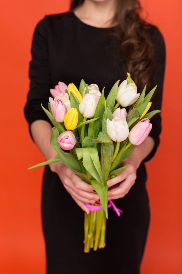Härlig flicka med en bukett av tulpan royaltyfri foto