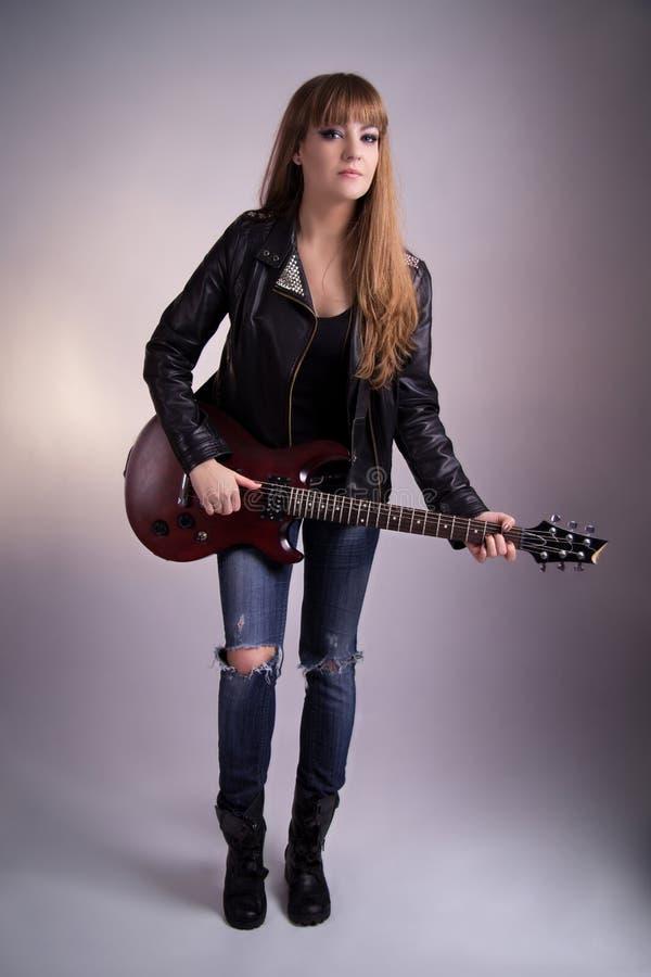 Härlig flicka med en elektrisk gitarr arkivbild