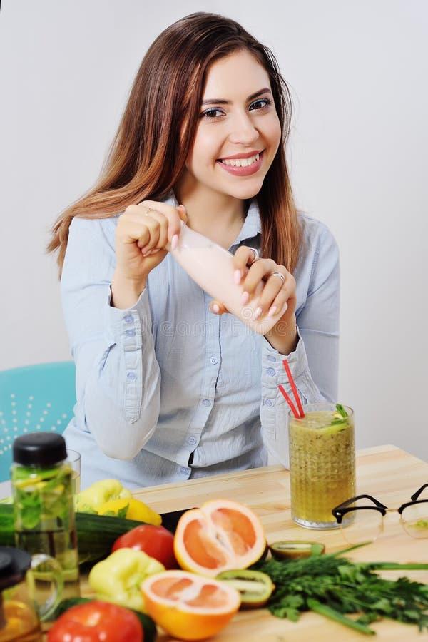 Härlig flicka med en flaska av yoghurt eller yoghurt i händer som ler på bakgrunden av en tabell med grönsaker och a royaltyfri foto