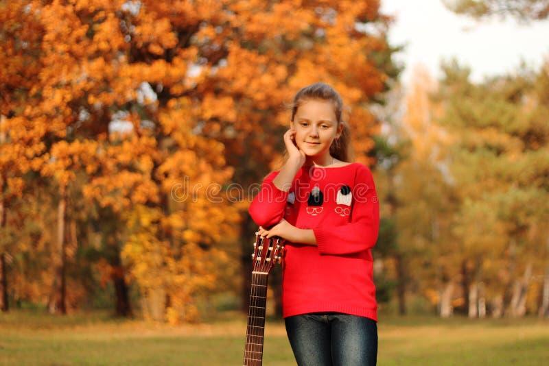 Härlig flicka med en gitarr i parkera royaltyfri fotografi