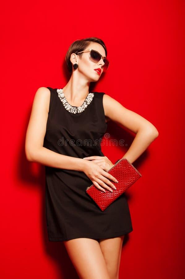 Härlig flicka med en kopplingpåse och solglasögon royaltyfri fotografi