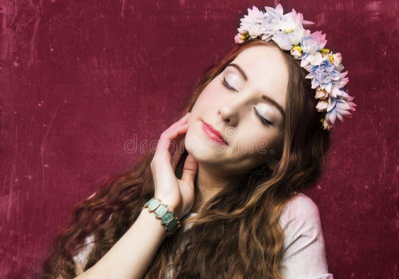 Härlig flicka med en krans av blommor arkivfoto