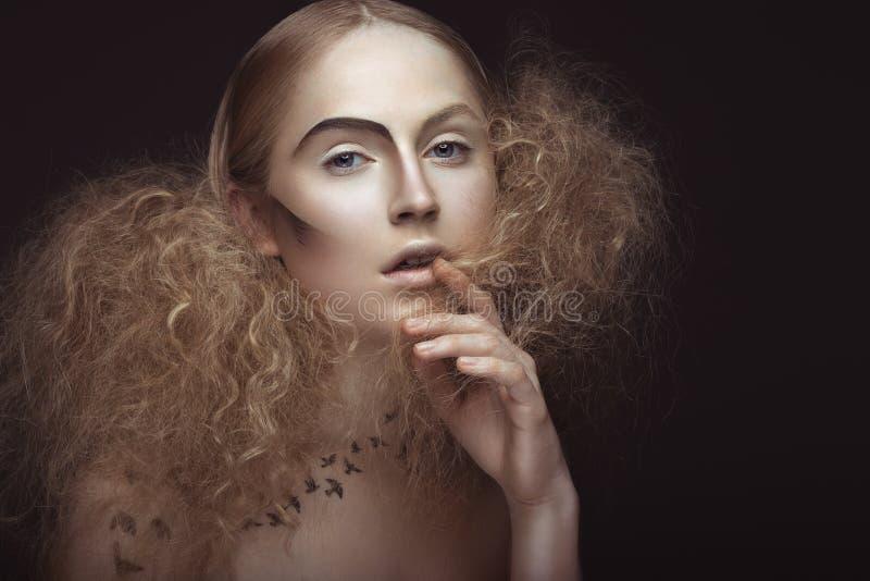 Härlig flicka med en modell på kroppen i form av den frodiga fåglar, idérik makeup och frisyren Härlig le flicka arkivfoton
