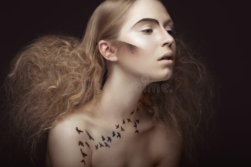 Härlig flicka med en modell på kroppen i form av den frodiga fåglar, idérik makeup och frisyren Härlig le flicka royaltyfria bilder