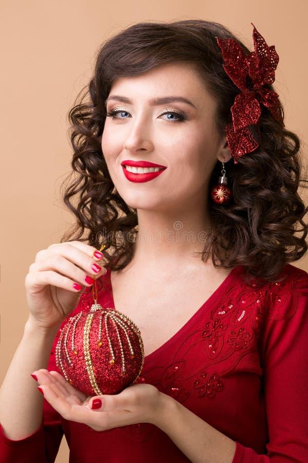 Härlig flicka med en röd julboll royaltyfri fotografi